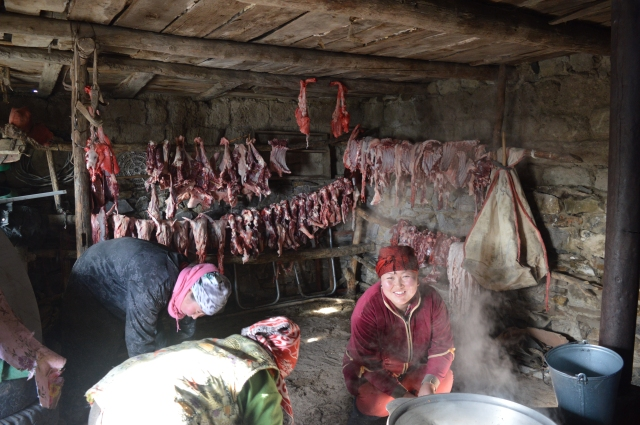 The women cleaning the digestive systems of the ten sheep whilst the meat is salted and hung behind.